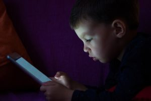Cute kid with tablet in the dark